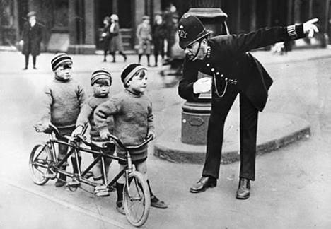 Vintage Mini Tridem ridden by kids talking with British Policeman
