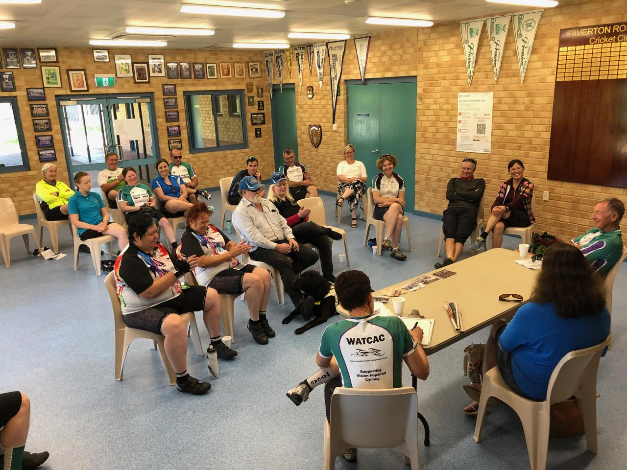 The Riverton sports pavilion room showing the AGM participants seated in front of the Erin, Jennifer and Trevor, while Trevor is completing his financial report