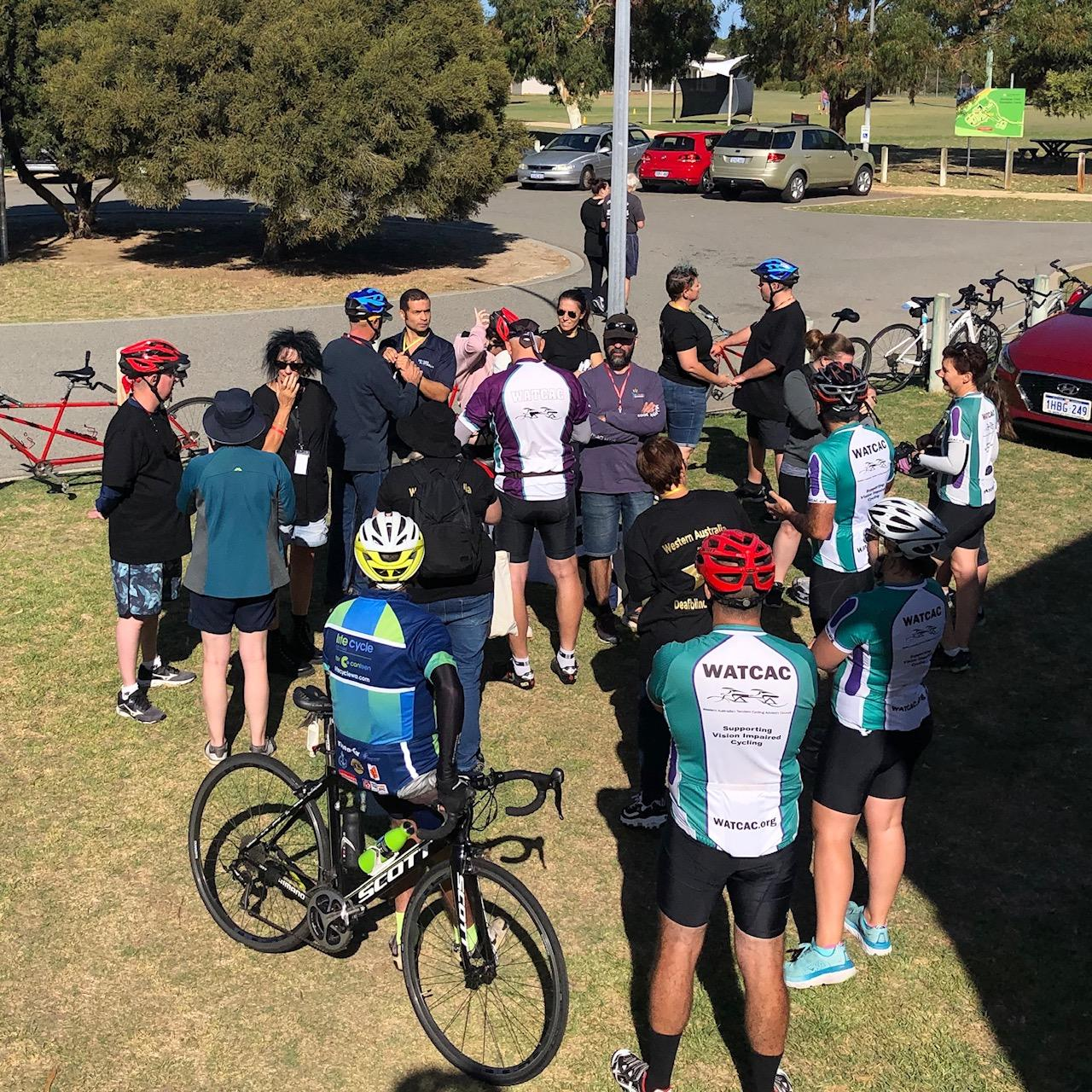 A group of a dozen or so people are standing outside in a loose cluster as Auslan interpreters and volunteer commguides run through the tandem cycling arrangements. A number of WATCAC volunteers are standing by to pair up and go riding!