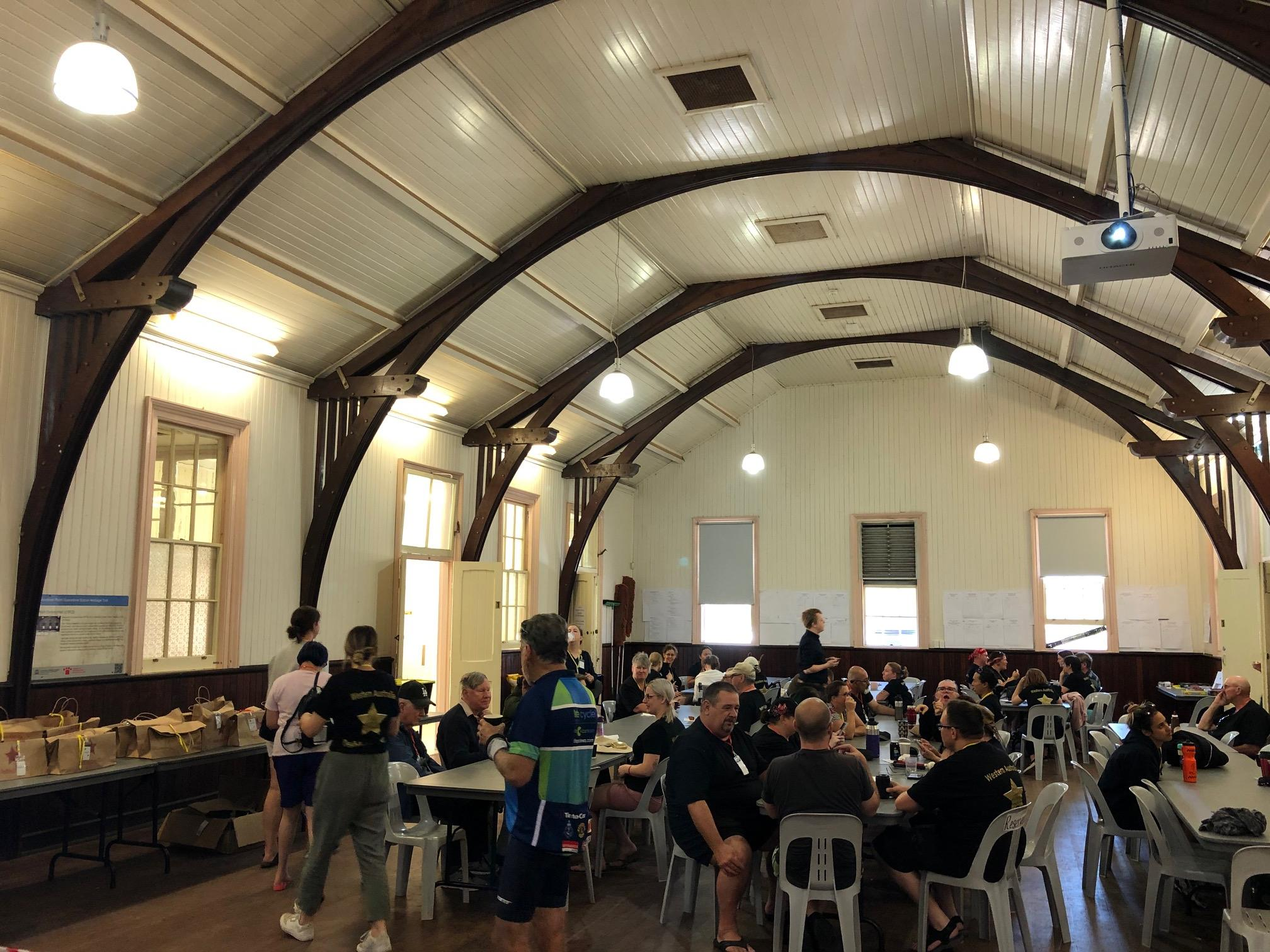 Around fifty people are seated at trestle tables beneath a very high timber paneled roof supported by four sturdy jarrah arches set with enormous curving beams.
