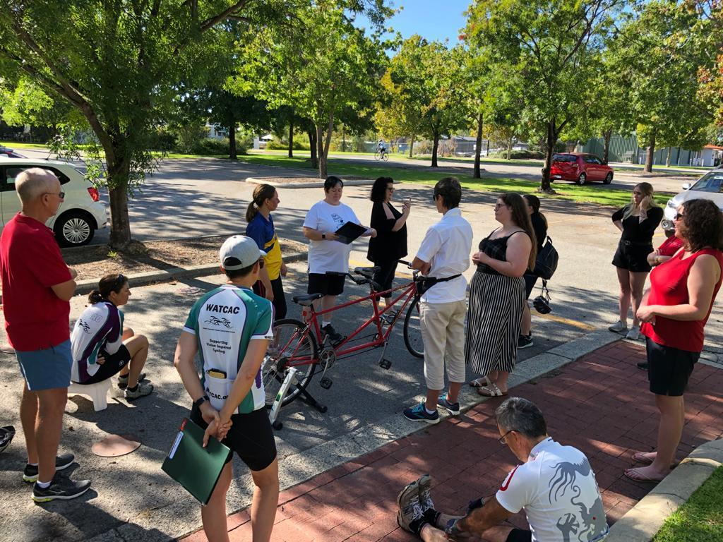 Saturday's new pilots, together with WATCAC volunteers, are standing around a stationary tandem to discuss its features and develop bike familiarity before their first ride.