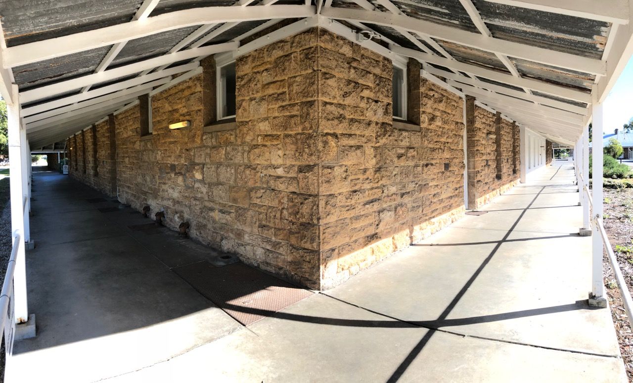 A view from the corner of one of the main blocks shows well crafted hand hewn limestone construction and iron roofed verandahs.