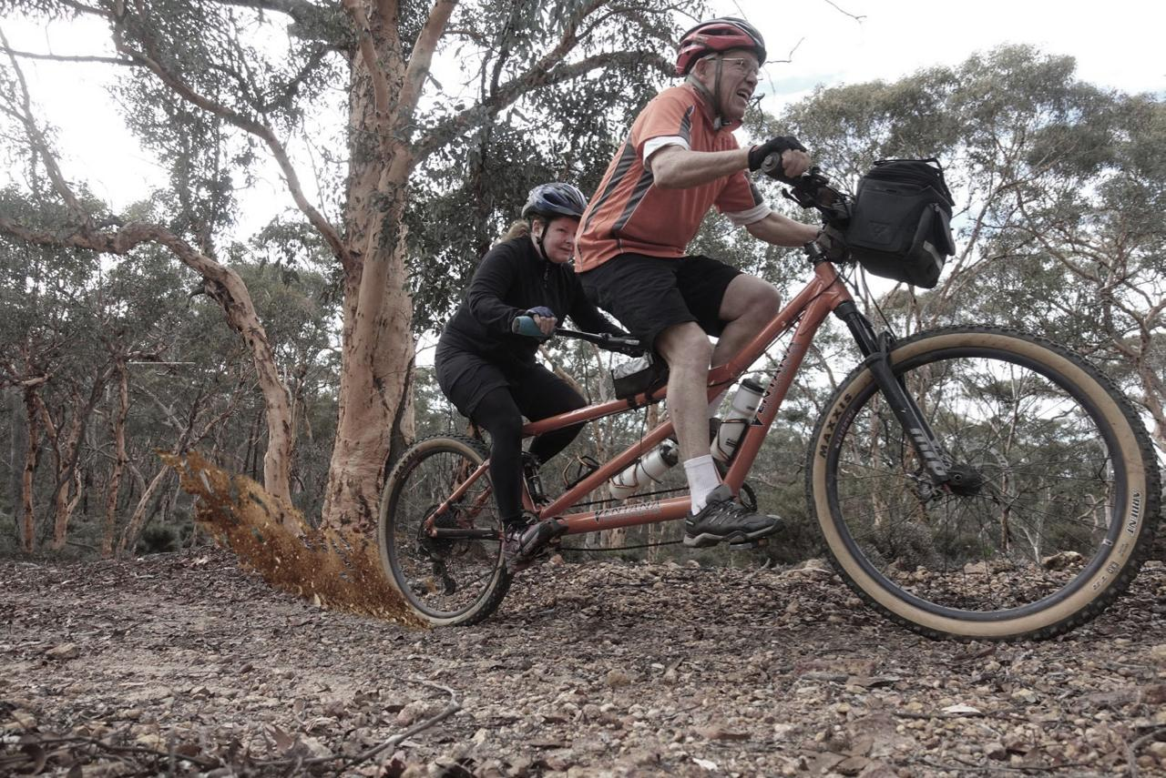 A sighted and VI tandem pair accelerate up a gravel trail to maintain momentum. A spray of dirt, a little artistic licence, is shown coming from the back wheel.