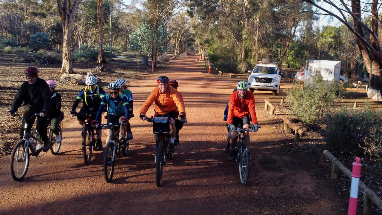 Four tandems and a single bike are riding side by side towards the camera, along the gravel road that runs through the Dryandra settlement. The long shadows and rugged up riders indicate it was an early start.